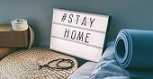 Coronavirus Yoga at home sign lightbox with text hashtag Hashtag STAYHOME glowing in light with exercise mat, cork blocks, strap meditation pillows. COVID-19 banner to promote self isolation staying at home