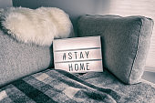 Coronavirus home lightbox sign with hashtag message Hashtag STAYHOME glowing on home sofa with cozy lambswool fur, blanket. COVID-19 text to promote self isolation staying at home