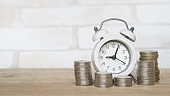 white analog clock and blurred stack of coins on wooden desk for finance and business concept