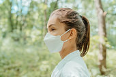 Asian woman wearing face mask walking in outdoor nature. Eco-friendly sustainable masks concept. Woman with korean kn95 mouth covering for corona virus prevention in forest.