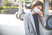 Virus mask Asian woman travel wearing face protection in prevention for coronavirus. Sick woman in public space bus station or airport. Air pollution, Coronavirus pandemic, environmental concept.