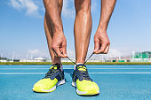 Runner tying running shoes laces on run tracks lanes in stadium getting ready for race competition outdoor on track and field. Sport athlete man jogging motivation