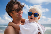 happy cute cheerful girl hugs father by the neck on the beach in summer, dad and daughter relax at sea