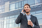 Man talking on smartphone. Businessman urban professional business man using mobile phone smiling drinking coffee at office building in city. Happy professional wearing suit jacket.