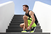 Runner man tying running shoes laces getting ready to run up the gym stairs training cardio hiit workout exercise on staircase. Acitve healthy lifestyle sport athlete, fitness motivation