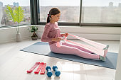 Home workout with resistance band fitness Asian woman training back muscles with rowing arm movement using rubber bands on yoga mat floor exercises with strap elastic