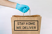 Home delivery food grocery delivered with gloves for COVID-19 quarantine from coronavirus social distancing. text message written : STAY HOME, WE DELIVER man giving bag as Corona virus prevention