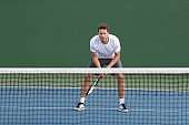 Professional tennis player man athlete waiting to receive ball, playing game on hard court. Fitness person focused behind net ready to return training cardio on outdoor sport activity