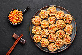 Shumai or Kanom Jeeb or Steamed Pork and Shrimp Dumplings on a black plate on dark slate backdrop. Chinese food. Asian Meal