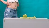 Female slimmed stomach and green apple in the foreground, selective focus. The concept of weight loss and proper nutrition
