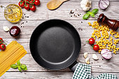 Empty frying pan with vegetables and dry pasta on wooden table