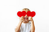 A little boy in a white shirt holds red hearts in his hands