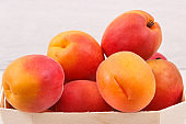 Apricot or peach in wooden box as healthy snack or dessert. Food containing vitamins and minerals