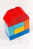 Colorful toy blocks and construction drawings of house. Building, buying or renting home concept