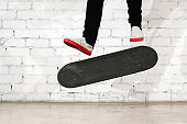 Skateboarder performing skateboard trick - kick flip on concrete. Olympic athlete practicing jump on white background, preparing for competition. Extreme sport, youth culture, urban sport