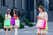 Happy shopping woman with a group of friends at the background. Retail, gesture and sale concept. Smiling teenage girl with many shopping bags at mall