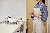 A woman operating home appliances with a smartphone