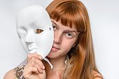 Mysterious woman cover her face behind a mask