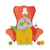 Knitting. Old female sitting in a cozy armchair knitting. Isolated flat vector illustration of a Granny knitting. The gray-haired grandmother holds in her hands clews and cat.