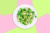 Lightly fried brussels sprouts on a white plate on the creative futuristic neon green and pink color drop with pentagons