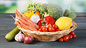 Fresh organic vegetables in basket on table and blur green background, Healthy food concept.