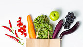 Various vegetables and fruits in a paper bag on white background close-up