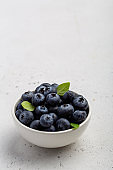 Blueberries in a bowl over light grey background