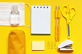 Stationery, notepad and medical mask on yellow background top view, copy space