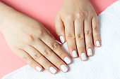 Beautiful women's hands with white manicure on pink and white background