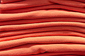 The orange-colored clothing is neatly folded into pile, front view, close-up