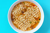 A bowl with ready instant noodles on blue background, top view