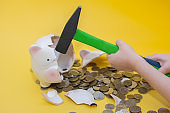 Children's hands hold a hammer and break the piggy Bank in the form of a pig. Coins spilled out , the piggy Bank broke. Close- up on a yellow background
