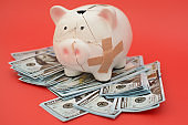 Piggy bank costs on paper money, dollars. The piggy bank was broken and collected back - it is a symbol of accumulated money.