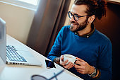 Charming caucasian bearded hipster sitting in his office, looking at laptop, holding coffee and taking a break.