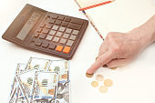 An elderly woman counts money using a calculator. There are coins and bills on the table. Saving money. Planning expenses in a crisis. Close-up photo, cropped.