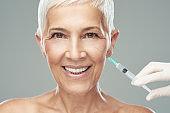 Beautiful smiling Caucasian senior woman standing in front of gray background and taking a shot of anti age product. Beauty photography.