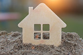 silhouette, shape in the form of a house on a pile of sand and blurred background. Concept - buying, selling real estate, mortgage, affordable housing. Horizontal photo, close-up