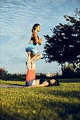 Two strong yogi women doing acro yoga outdoors.