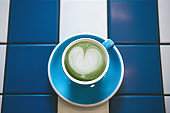 Closeup fresh fragrant healthy green Matcha latte tea in a blue mug on a table of blue and white ceramic tiles