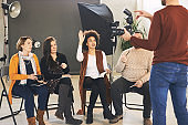 Young mixed race woman asking tutor questions about photography.