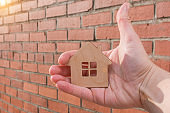 close-up of a small wooden house in hand against a brick wall background. Concept - security, purchase, construction of real estate, investment of effort and money, everything is in our hands.