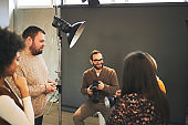 Young attractive bearded tutor sitting on chair in studio, holding camera and explaining something about photography while attendees standing and looking at him.