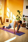 Mid-adult fit pregnant Caucasian woman practicing prenatal yoga exercises in home environment. Morning time.