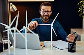 Young creative caucasian bearded environmentalist  with curly hair sitting in his office, touching windmill model and drawing new better model in notebook.
