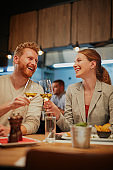Young smiling, happy couple in love sitting in restaurant for dinner and toasting with white wine.