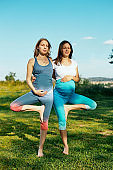 Two pregnant women doing acro yoga outdoors.