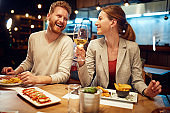 Smiling cheerful couple sitting in a restaurant, having dinner and chatting. Man talking to a woman while a woman listening to him and drinking white wine.