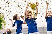 Sport team celebrating success. Happy boys rising golden trophy on celebration. Children winning sports soccer tournament competition. Inter-school soort competition