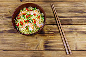 Bowl of instant Chinese noodles with shrimps, green onion and red hot chilli peppers on wooden table. Top view