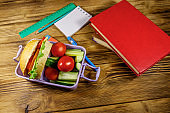 Back to school concept. School supplies, books and lunch box with burgers and fresh vegetables on a wooden table